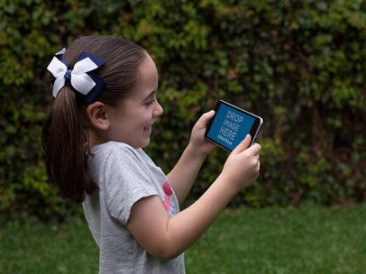 Little Girl Playing on her Black iPhone 7 Plus in Landscape Position Mockup in the Back Yard a13003