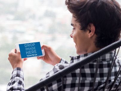 Mockup of a Young Man Staring at an iPhone in Landscape Position with Blurry Background 13038