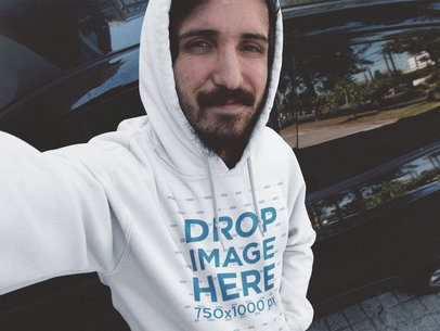 Hoodie Mockup Featuring a Young Man with a Beard Leaning Against a Car a12900
