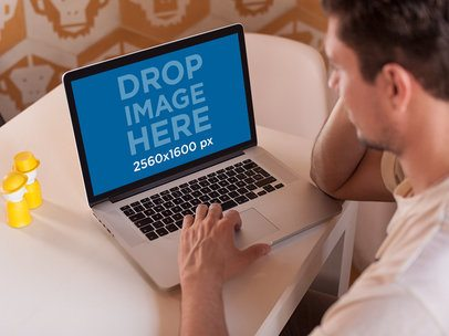Young Man Using His MacBook Pro While Sitting On His Table Mockup a14122