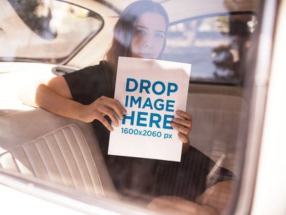 Mockup of a Girl Holding a Big Book While Inside a Car a14399