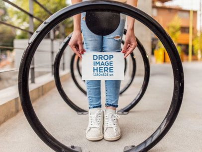Girl Holding a Half Letter Flyer Mockup While at the Bike Station a14807