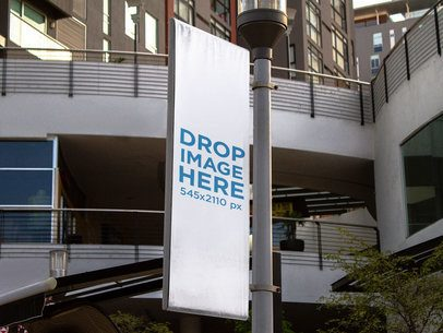 Vertical Banner Template Hanging from a Light Pole Near a New Building a15167